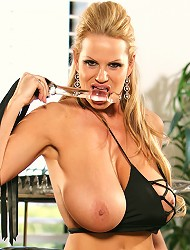 Kelly uses a leather and crystal dildo while...